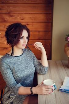 Leuke vrouw koffie drinken in witte kop in café op stad. fall casual mode, elegante alledaagse look. plus size model.