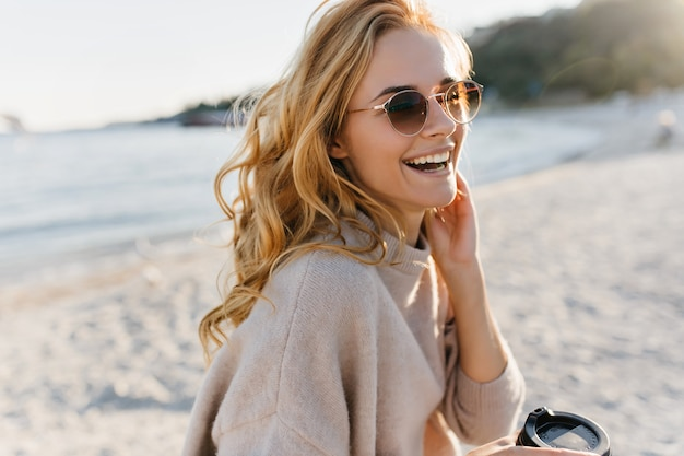 Leuke vrouw lacht echt, ontspannen op het strand. blinde vrouw in glazen en trui houdt kopje koffie.