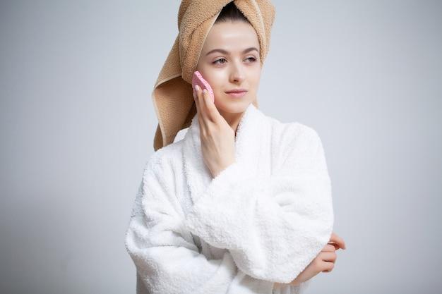 Leuke vrouw maakt make-up op het gezicht in de badkamer
