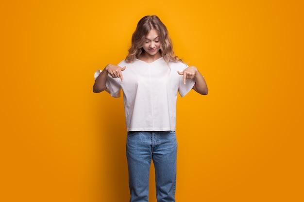 Leuke vrouw met blond krullend haar dat naar beneden wijst en een wit t-shirt en een spijkerbroek draagt die zich voordeed op een gele muur