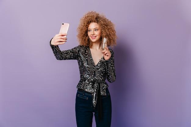 Leuke vrouw met blonde krullen gekleed in zwarte lovertjes top met glas champagne en selfie maken op paarse ruimte.