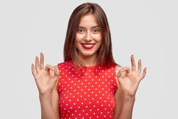 Leuke vrouw met charmante vriendelijke glimlach, maakt oke gebaar, gekleed in modieuze polka dot jurk, toont goedkeuring, poseert tegen witte muur. jonge vrouw met rode lippen modellen binnen.