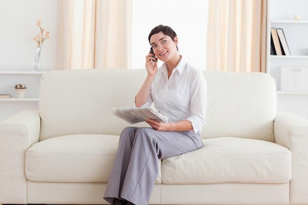 Leuke vrouw met een mobiel en een krant