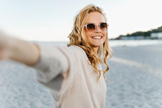 Leuke vrouw met golvend blind haar glimlacht oprecht en neemt selfie op zee.