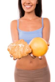 Leuke vrouw met grapefruit en croissant