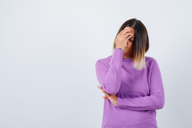 Leuke vrouw met hand op gezicht in paarse trui en boos kijken. vooraanzicht.