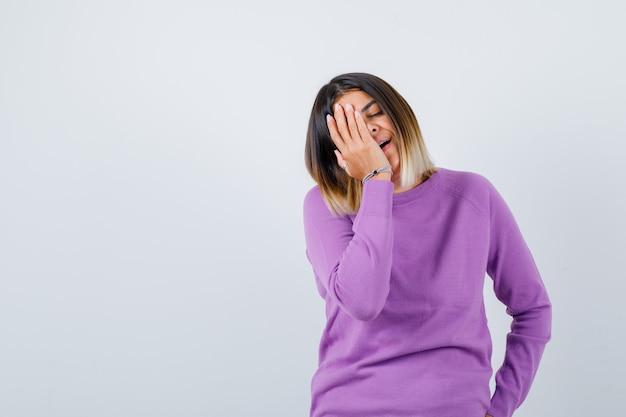Leuke vrouw met hand op gezicht in paarse trui en vrolijk op zoek. vooraanzicht.