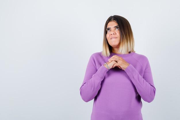 Leuke vrouw met handen over de borst, omhoog kijkend, lip bijtend in paarse trui en er dromerig uitzien. vooraanzicht.