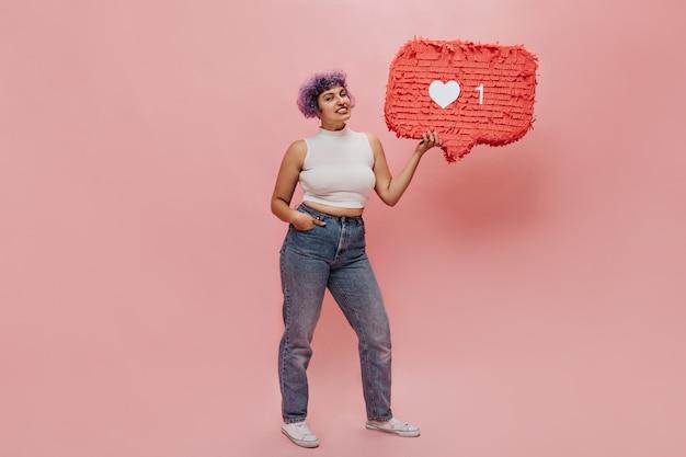 Leuke vrouw met heldere ongebruikelijke haren poseert met een hand in haar zak en een ander vasthoudend teken zoals op roze