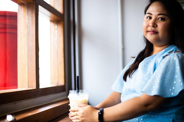 Leuke vrouw met overgewicht in koffiecafé, gelukkige aziatische vrouw in een café met plastic kopje koffie