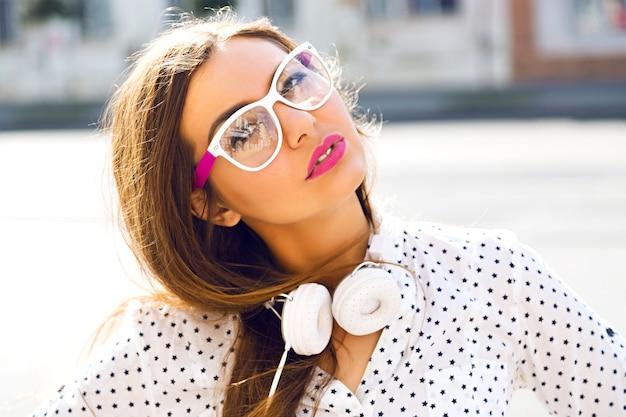 Leuke vrouw met plezier op straat, gekleed in witte grappige jurk en witte koptelefoon