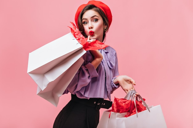 Leuke vrouw met rode lippenstift kijkt naar de camera en vormt met witte grote tassen na goed winkelen.