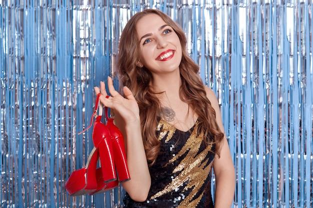 Leuke vrouw met schoenen over blauwe achtergrond met decor regen, met rd schoenen met hoge hakken, glimlachend op zoek, ziet er gelukkig uit