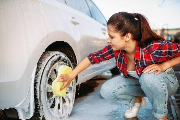 Leuke vrouw met spons autowiel schrobben met schuim, autowasserette. dame op zelfbedieningsautowassen. buiten carwash op zomerdag