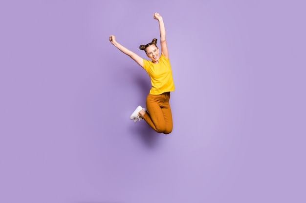 Leuke vrouw met topknopen poseren tegen de paarse muur