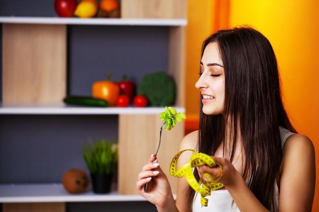 Leuke vrouw met verse groenten en fruit leidt een gezonde levensstijl