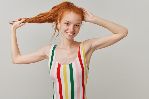 Leuke vrouw, mooi roodharig meisje met paardenstaart en sproeten, gestreepte kleurrijke zwembroek dragen