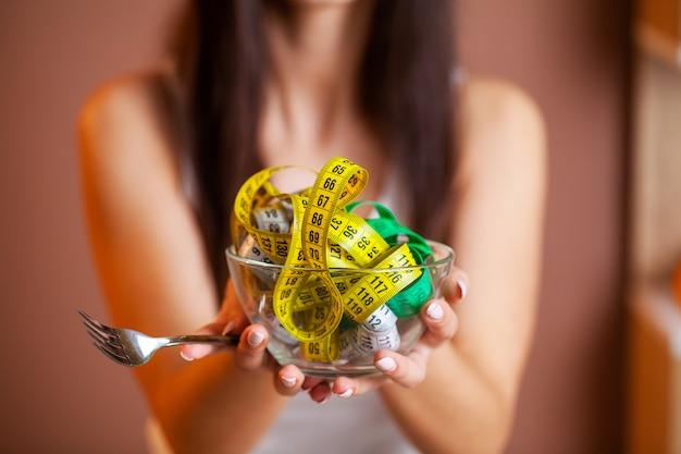 Leuke vrouw op een dieet dat een bordhoogtepunt van band houdt.