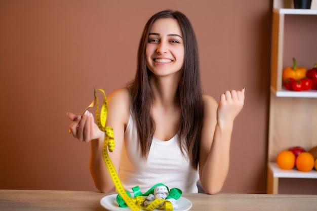 Leuke vrouw op een dieet dat een bordhoogtepunt van band houdt