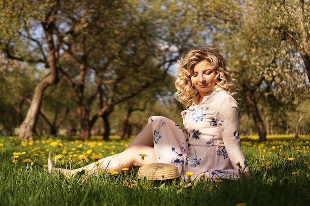 Leuke vrouw rust in het groene zomerpark met paardebloemen