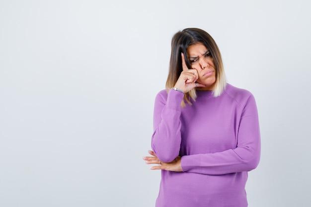 Leuke vrouw staat in denkende pose in paarse trui en ziet er somber uit, vooraanzicht.