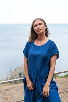 Leuke vrouw staat in een blauwe jurk tegen de achtergrond van de zee en de lucht peinzende gezichtsuitdrukking en...