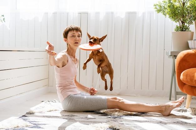 Leuke vrouw traint haar hond thuis terwijl ze op de vloer zit. kaukasisch meisje leert dierentrucs en...
