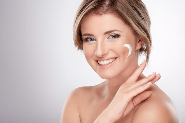 Leuke vrouw van gemiddelde leeftijd met naakte make-up en blote schouders, concept van schoonheidsfoto, behandeling van huid en rimpels, uv-bescherming, met behulp van crème, maansymbool.