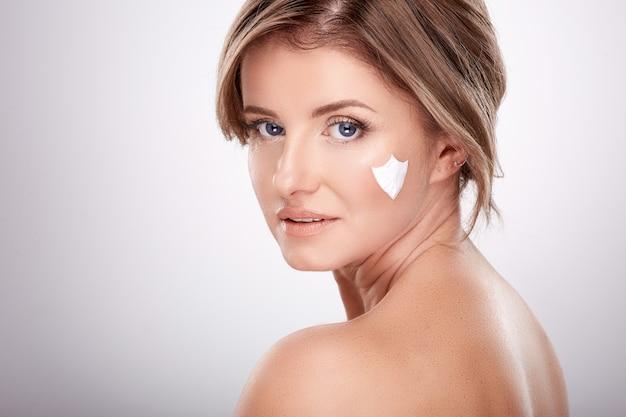 Leuke vrouw van gemiddelde leeftijd met naakte make-up en blote schouders, concept van schoonheidsfoto, behandeling van huid en rimpels, uv-bescherming, met behulp van crème