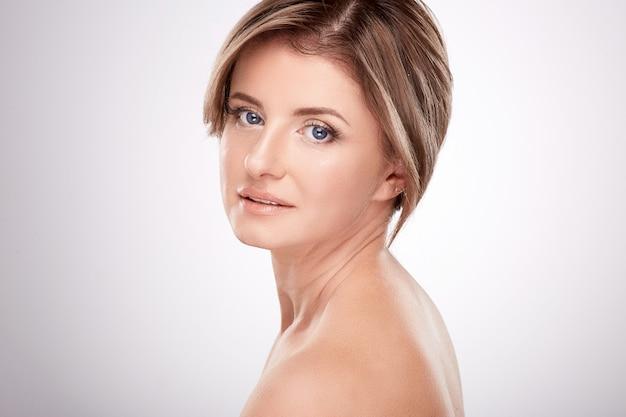 Leuke vrouw van gemiddelde leeftijd met naaktmake-up en naakte schouders poseren muur, schoonheid foto concept, huid en rimpels behandeling.