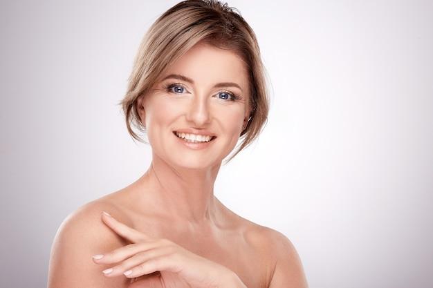 Leuke vrouw van gemiddelde leeftijd met naaktmake-up en naakte schouders poseren muur, schoonheidsfoto concept, huid en rimpels behandeling, glimlach.