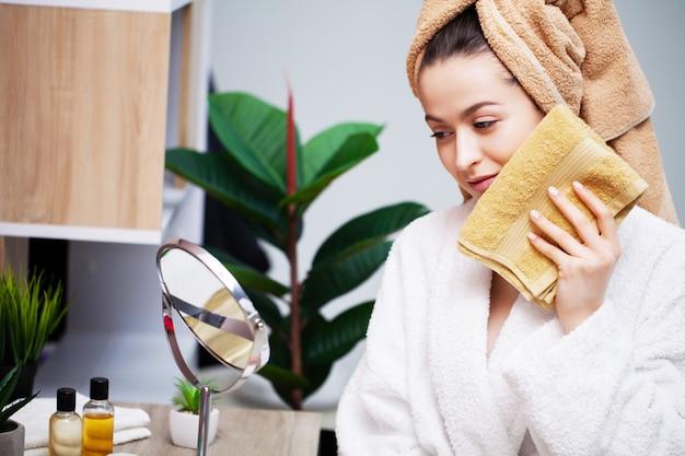 Leuke vrouw veegt het gezicht handdoek na het douchen af