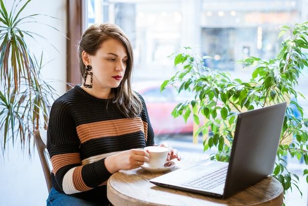 Leuke vrouw zittend aan een tafel in een café met een laptop koffie drinken