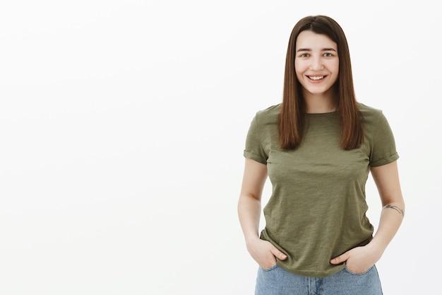 Leuke vrouwelijke collega met ambitieuze blik hand in hand in zakken wachtend op opdracht, glimlachend in het algemeen ontspannen en gelukkig gevoel over grijze muur met olijfgroen t-shirt