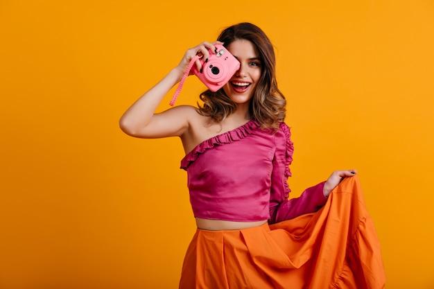Leuke vrouwelijke fotograaf die in studio glimlacht