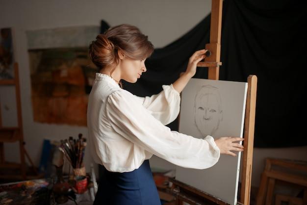 Leuke vrouwelijke kunstenaarstekening in studio. creatieve verf, potloodschets op ezel, workshopinterieur op achtergrond