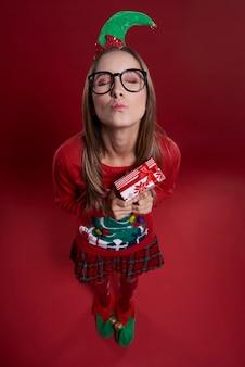 Leuke vrouwelijke nerd met klein cadeautje gekleed in kerstkleren