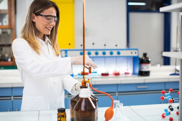 Leuke vrouwelijke onderzoeker in beschermende werkkleding in laboratorium analyseren kolf