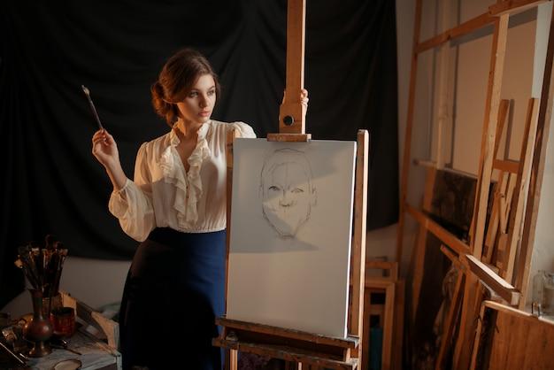 Leuke vrouwelijke schilder met borstel die zich tegen ezel in studio bevindt. creatieve verf, vrouw tekening potloodschets, workshop interieur op achtergrond
