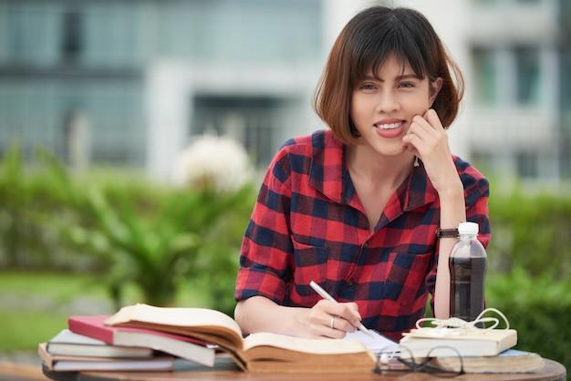 Leuke vrouwelijke student die voor examen in openlucht voorbereidingen treft