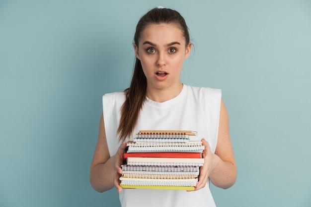 Leuke vrouwelijke student met een berg notitieboekjes en boeken in haar handen