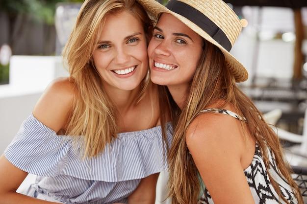 Leuke vrouwen hebben echte vriendschap, brengen zomervakanties samen door, zijn blij om gefotografeerd te worden, hebben een aantrekkelijk uiterlijk en plezier samen, dragen stijlvolle kleding. mensen, relaties en geluksconcept
