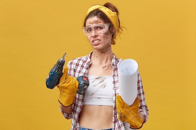 Leuke vrouwenbouwer die een beschermende bril, handschoenen en een geruit overhemd draagt met boor en blauwdruk, terughoudend om haar flat te repareren, kijkt met grote onwil en wanhoop