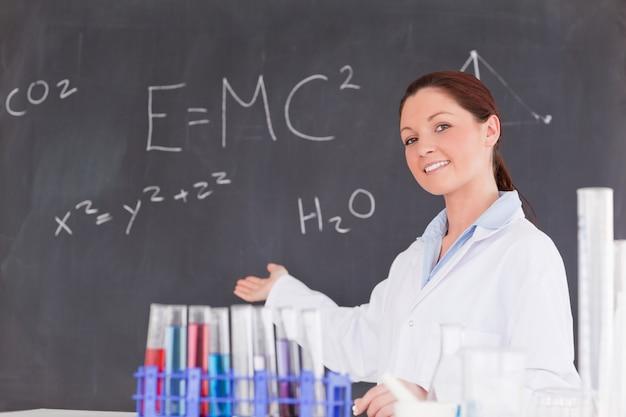 Leuke wetenschapper die de vergelijkingen op een bord toont