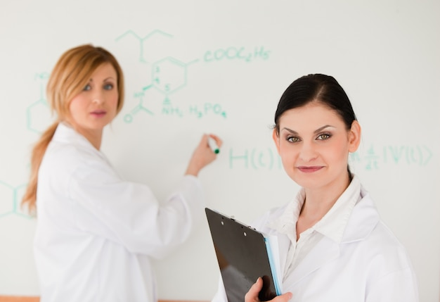 Leuke wetenschapper die een formule schrijft, geholpen door haar assistent