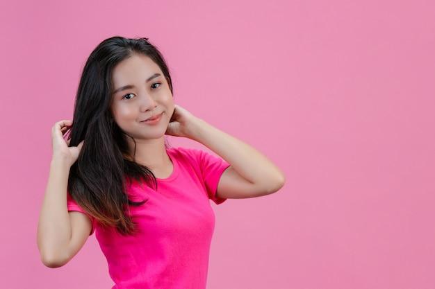 Leuke witte aziatische vrouw stelt zich met een roze haar op een roze.