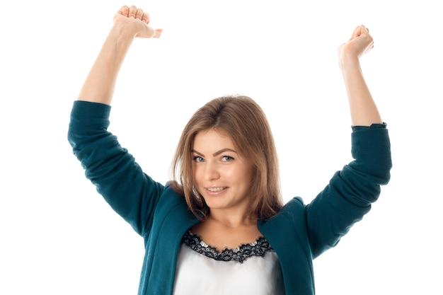 Leuke zakenvrouw in blauwe jas met armen omhoog kijken naar de camera en glimlachend geïsoleerd op een witte achtergrond