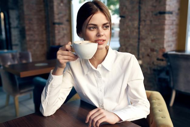 Leuke zakenvrouw zittend in een café aan de tafel een kopje drank levensstijl