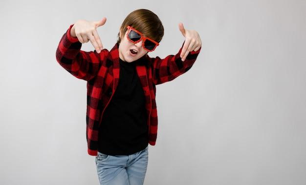 Leuke zekere kleine kaukasische jongen in geruit overhemd in rode zonnebril die op grijs voor de gek houden