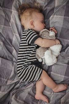 Leuke zes maanden oude blonde jongen die op een grijs bed met een stuk speelgoed in zijn handen slaapt